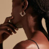 Model faces away with gold earring.