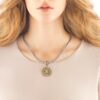 Woman wearing a gold pendant necklace.