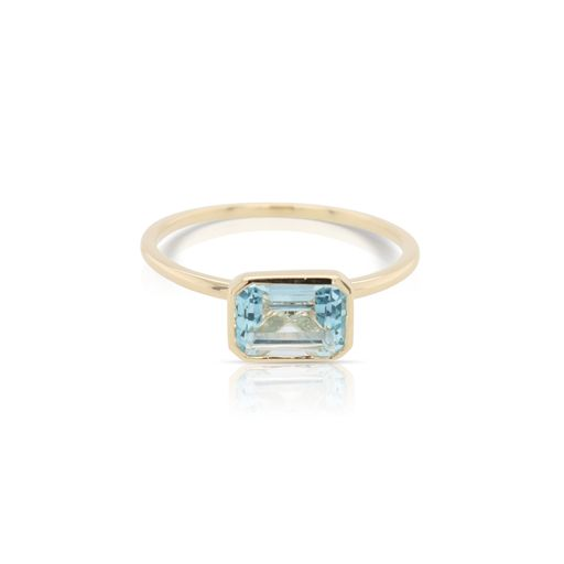 This solitaire blue topaz ring by Rafael is crafted from 14k yellow gold and features a 1.45 carat emerald cut blue topaz.