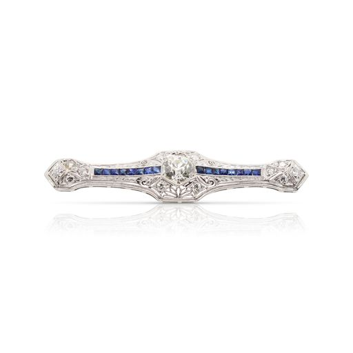 This sapphire and diamond pin is crafted from platinum and features a 1.18 carat center diamond, 0.40 total carats of accent diamonds and 1.00 total carats of sapphires.