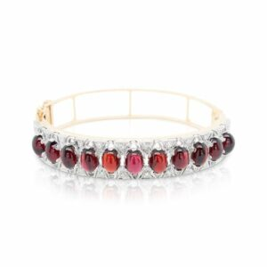 This garnet and diamond bracelet is crafted from 14k yellow gold and features oval garnets and 0.20 total carats of diamonds.