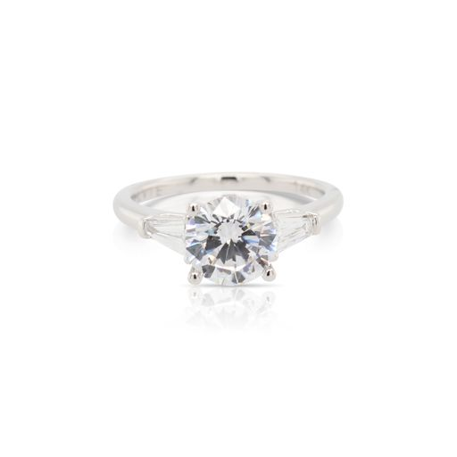 This diamond engagement ring mounting is crafted from 14k white gold and features 0.34 total carats of tapered baguette side diamonds. The center diamond is chosen separately.
