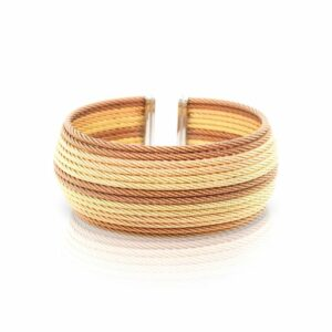 This cuff bracelet by Charriol is crafted from steel, bronze, and 18k yellow gold and features 14 rows of multi colored cable.