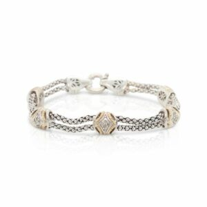 This engraved diamond station bracelet is crafted from sterling silver and 14k yellow gold and features diamond accents in each engraved station.