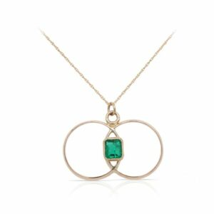 This double circle emerald necklace is crafted from 14k yellow gold and features a cushion cut emerald.